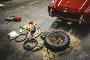 Car Parts on the floor behind a red car.